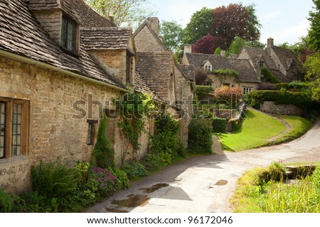 Traditional Cotswold cottages in England, UK.  after the rain. spring. Bibury is a village and civil parish in Gloucestershire, England. - stock photo