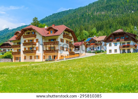 Traditional countryside houses in alpine village on shore of Weissensee lake in summer landscape of Alps Mountains, Austria - stock photo