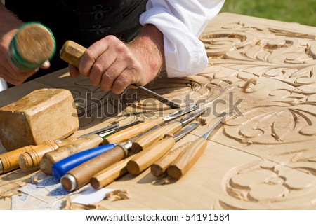 Traditional craftsman carving wood with floral motifs - stock photo