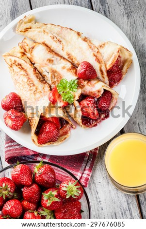 Traditional crepes served with strawberries on a plate