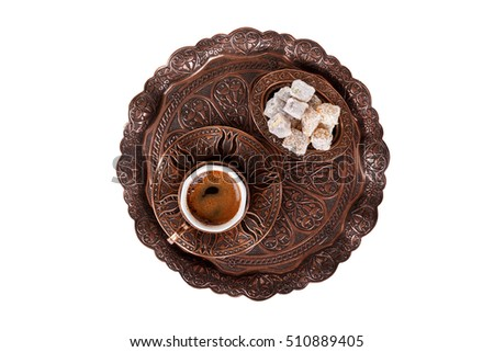 Traditional cup of Turkish coffee with foam and Turkish delights, top view, isolated on white background.