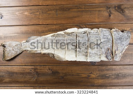 Traditional cut of salted cod on a wooden board - stock photo