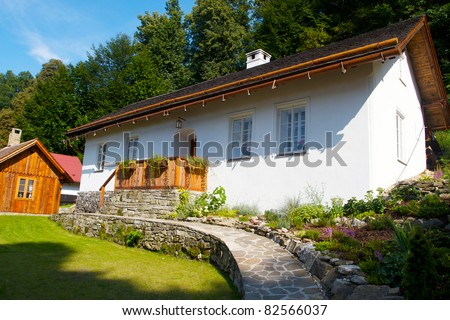 Traditional czech house/cottage at village nearby forest painted on white in mid summer - stock photo