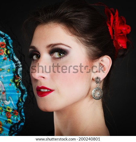 Traditional dance. Portrait of spanish girl attractive woman flamenco dancer with fan on black. - stock photo