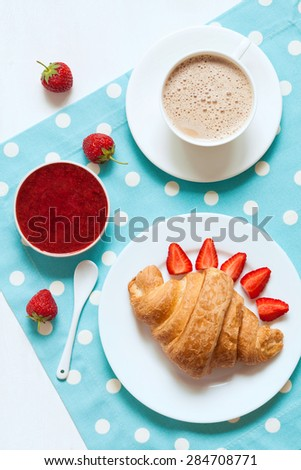 Traditional delicious croissant French sweet dessert with a cup of coffee, fresh strawberry and jam on provence style background. Rustic style and natural light. Vivid colors. - stock photo