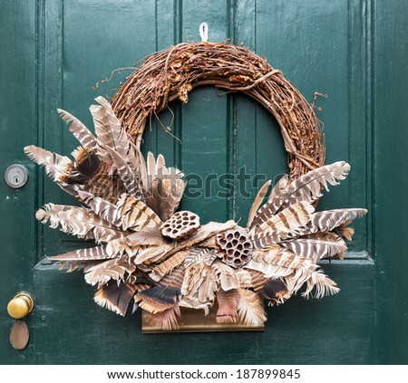 Traditional design of a christmas wreath attached to the front door of old house - stock photo