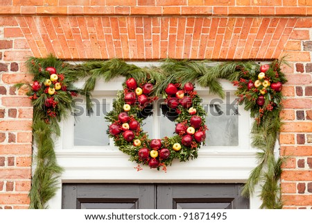 Traditional design of a christmas wreath attached to the front of old house - stock photo