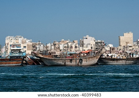 Traditional Dhow boats laden with goods at docks in Dubai - stock photo