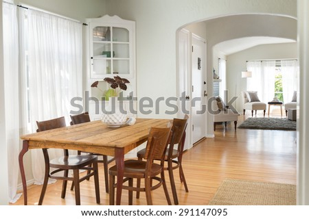 Traditional dining room with wooden table with chairs and built ins next to living room.  - stock photo