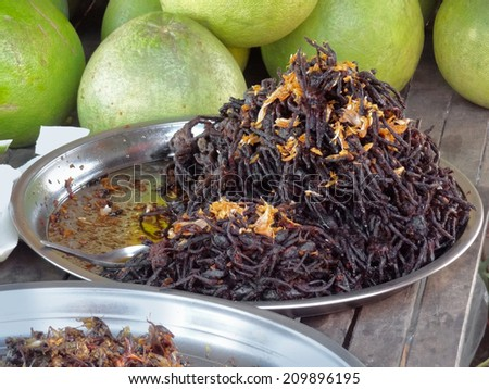traditional dish in Thailand showing lots if fried bird spiders - stock photo