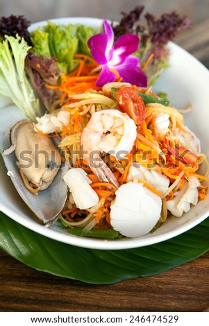 Traditional dish of freshly prepared Thai food.  Thai seafood and som tum green papaya salad. - stock photo