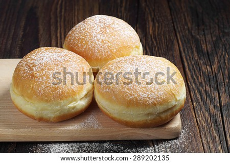 Traditional doughnuts with powdered sugar on wooden table  - stock photo