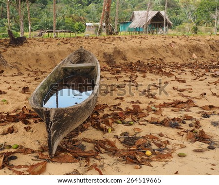 Traditional dugout canoe on the beach near a Ngobe Bugle (aka Guaymi) community about 30 miles south of Bocos del Toro, on the north eastern Caribbean coast of Panma - stock photo