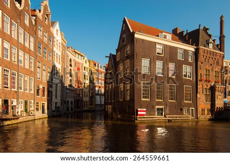 Traditional Dutch buildings reflecting on canal water at sunset - stock photo