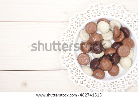 Traditional Dutch chocolate candy pepernoot on white plate on white wooden background