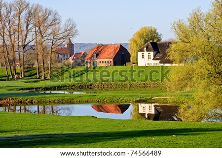 Traditional Dutch village Ooij protected by a dike to prevent flooding by the river Waal - stock photo