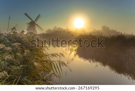 Traditional dutch Windmill in a dewy marshland area on a foggy morning in september - stock photo