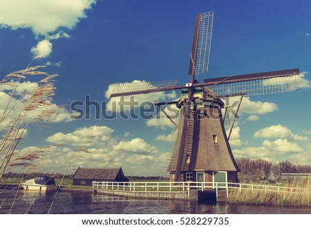 Traditional dutch windmill near the canal. Netherlands (Vintage Style)