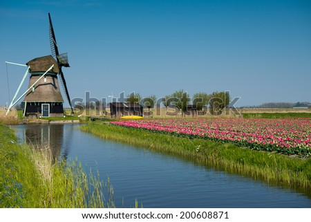 Traditional Dutch windmill near the channel. Netherlands. - stock photo