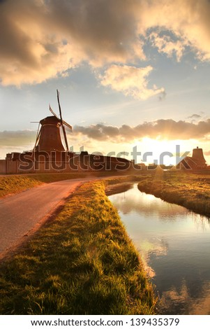Traditional Dutch windmills with canal against sunset in Amsterdam area, Holland - stock photo