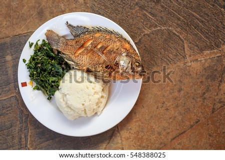 Traditional East African food - ugali, fish and greens