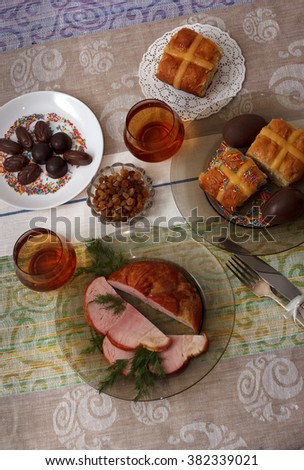 Traditional easter dinner set with sliced meat, bread with herbs, handmade colored eggs, chocolates, easter cake and glasses of juice on colorful tablecloth, top view - stock photo
