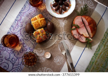 Traditional easter dinner set with sliced meat with herbs, chocolate eggs, easter cake and glasses of juice and a candle on colorful tablecloth, horizontal top view - stock photo