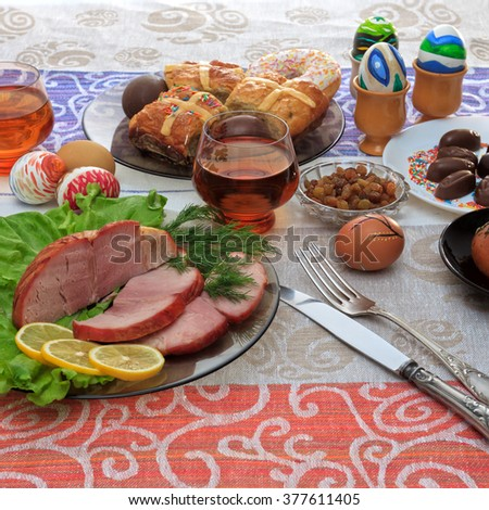 Traditional easter dinner set with sliced meat with lemon and herbs, bread, handmade colored eggs, chocolates, raisins, easter cake and glasses of juice on colorful tablecloth, close up view - stock photo