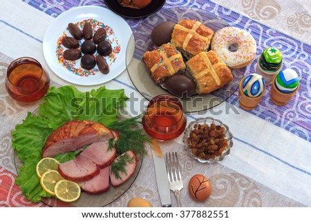 Traditional easter dinner set with sliced meat with lemon and herbs, handmade colored eggs, chocolates, raisins, easter cake and glasses of juice on colorful tablecloth, horizontal top view - stock photo