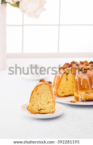 Traditional easter yeast cake covered with white icing and raisins Spongy yeast cake that is traditionally baked for Easter Sunday in Poland, Belarus, Ukraine , Russia. Cup of coffee white background - stock photo