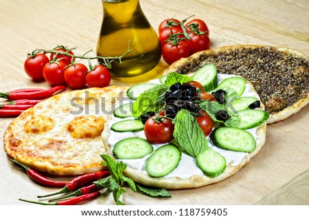 Traditional Eastern plate of manaqish,flat bread topper with cheese and different ingredients. - stock photo