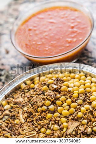 Traditional Egyptian dish of rice, macaroni and lentils mixed together, with tomato sauce, chickpeas and fried onions - stock photo