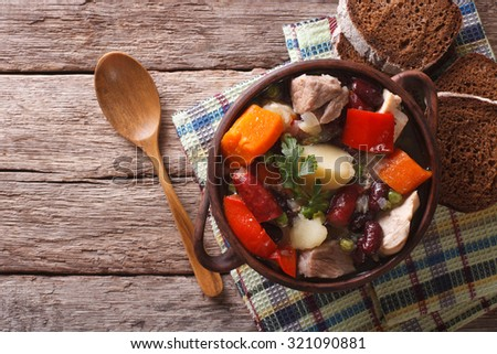 Traditional eintopf soup with meat, sausages and vegetables in the pot on the table. horizontal top view