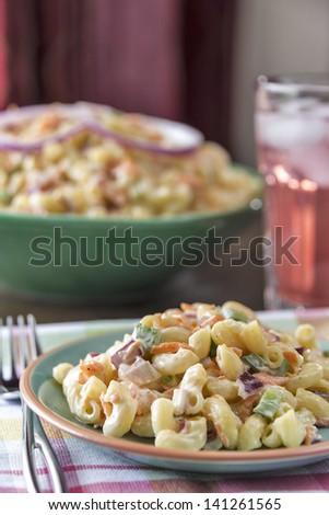 Traditional elbow style macaroni salad served with a glass of pink lemonade. - stock photo