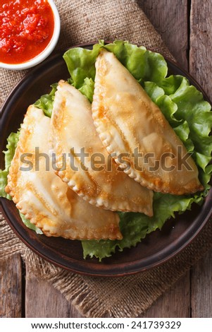 Traditional empanadas on a plate and sauce closeup. vertical view from above   - stock photo