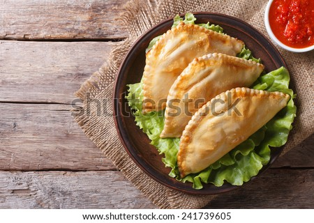 Traditional empanadas on a plate and sauce. horizontal view from above, rustic style  - stock photo