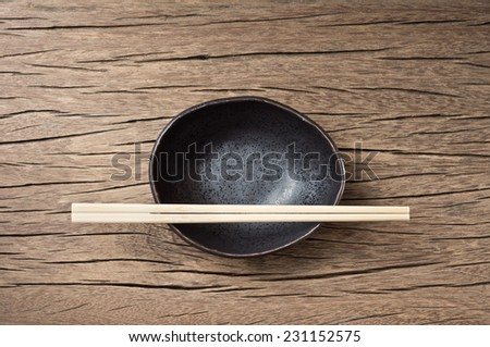 traditional empty rice bowl with bamboo chopsticks on old wood plank - stock photo