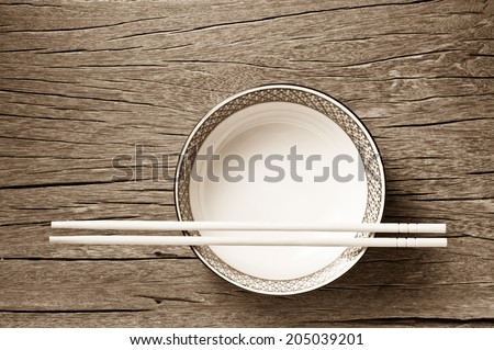 traditional empty rice bowl with bamboo chopsticks on old wood plank in sepia color tone - stock photo