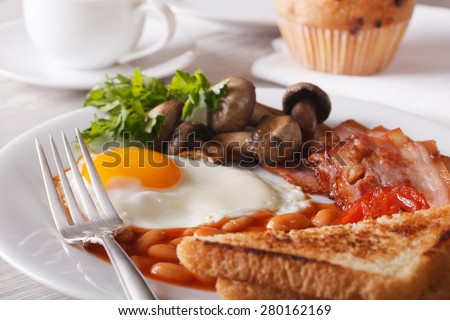 Traditional English breakfast: eggs with bacon and vegetables close-up on a plate. horizontal  - stock photo