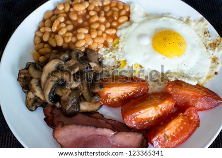 Traditional English breakfast - tomatoes, fried bacon, mushrooms, eggs and tomato baked beens - stock photo
