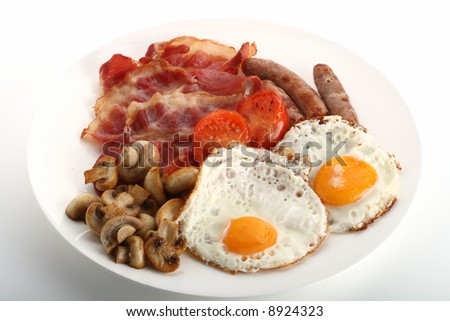 Traditional English breakfast - tomatoes, fried sausages, bacon, mushrooms, eggs - stock photo