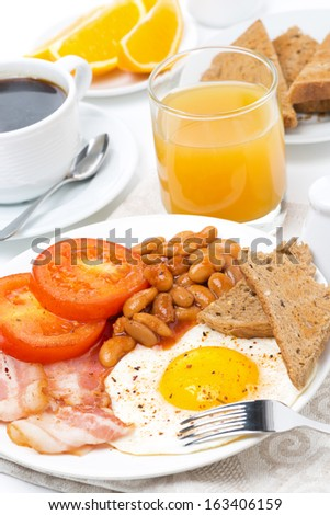 Traditional English breakfast with fried eggs, bacon, beans, coffee and juice, vertical close-up - stock photo