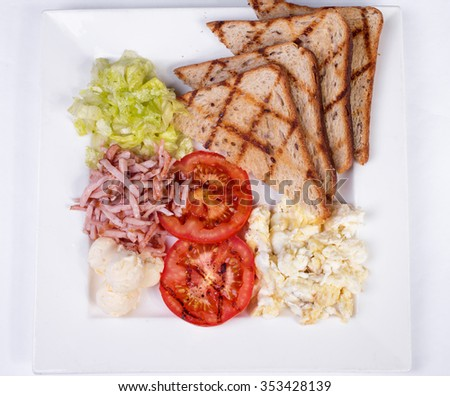 Traditional English breakfast with scrambled eggs, tomatoes, potatoes, toast and fresh salad on a white background