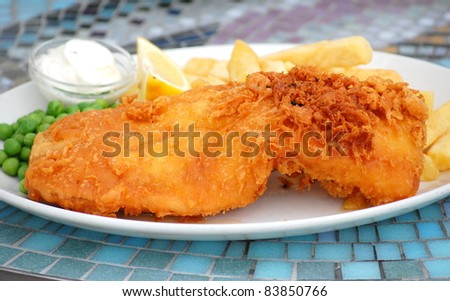 Traditional English Fish and Chips on a plate.  Battered Fish at the front. - stock photo