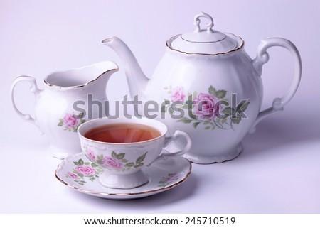 Traditional english tea with white tea set floral dishware  - stock photo