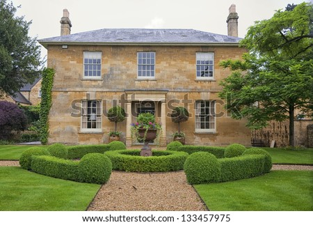 Traditional English village house with a beautiful garden. - stock photo