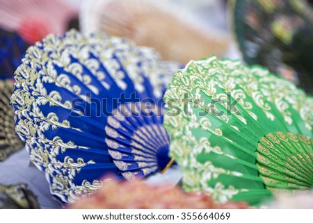 Traditional fans, now being sold as souvenirs, lying on the ground, ready for sale - stock photo