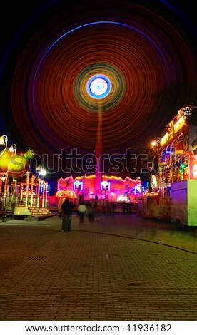 Traditional festival in Prague in night hours. Long exposure turnd people to ghosts and a ferris wheel in the show of neons