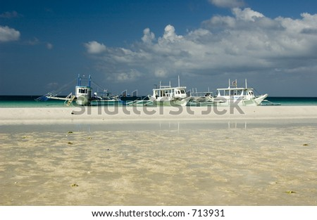 Traditional filipino outrigger boat  laying on the white beach at Boracay island Philippines
