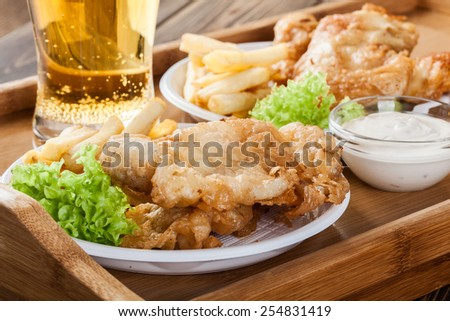 Traditional fish and chips with tartar sauce on a tray